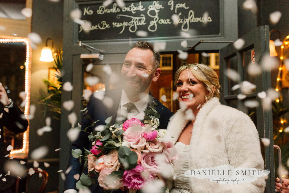 bride and groom arriving at london pub with confetti