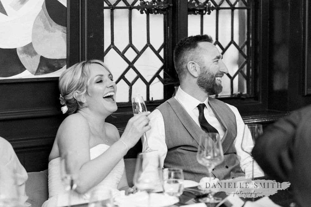 bride and groom laughing at speeches - chilled london wedding