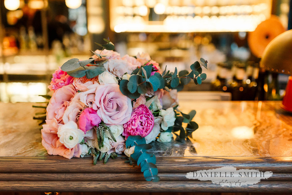 pink and ivory wedding bouquet on bar