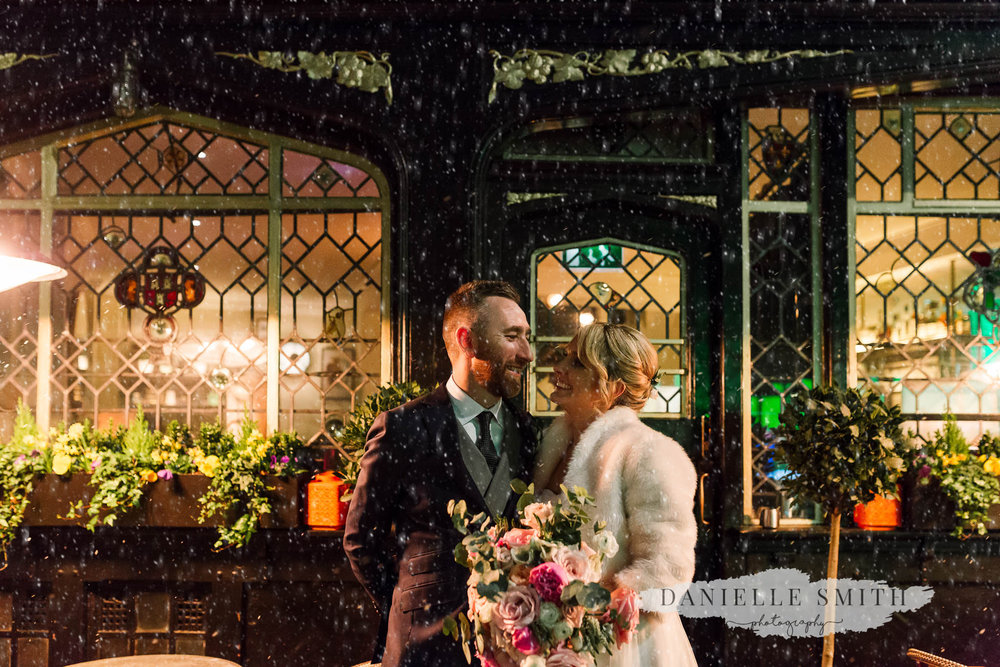 bride and groom outside clarette wine bar in snow