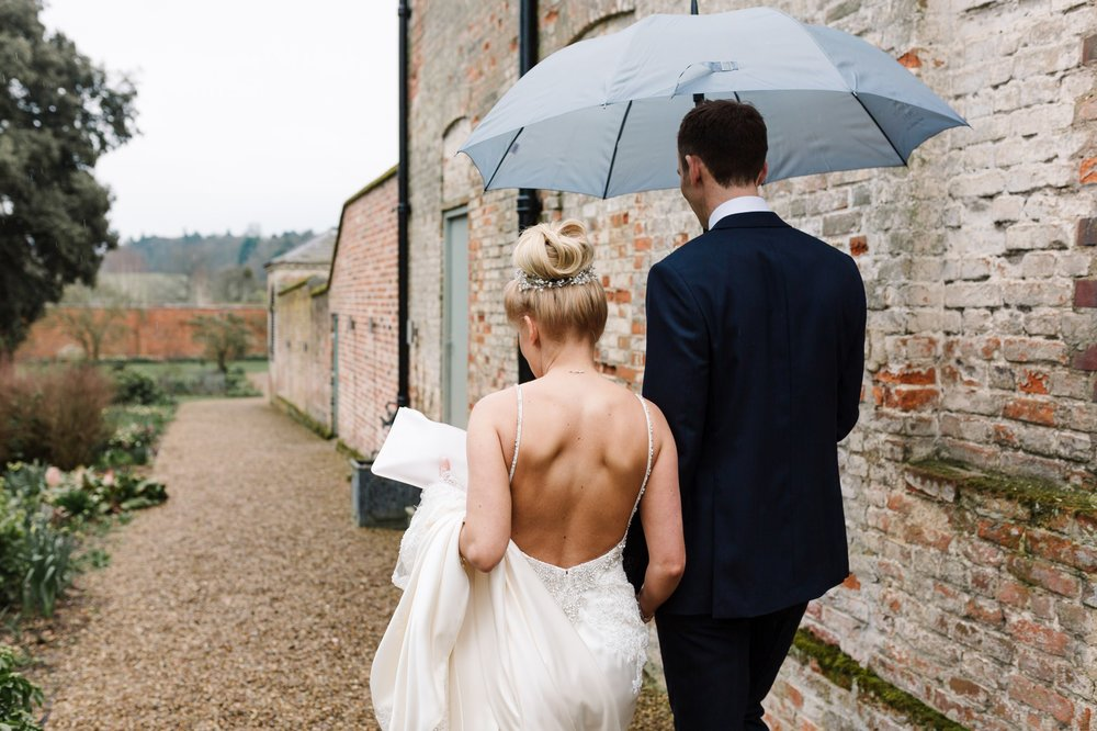 bride and groom walking in rain at braxted park