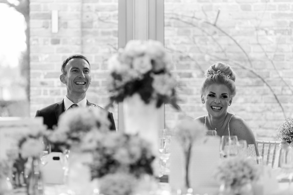 bride and groom laughing at speeches at braxted park