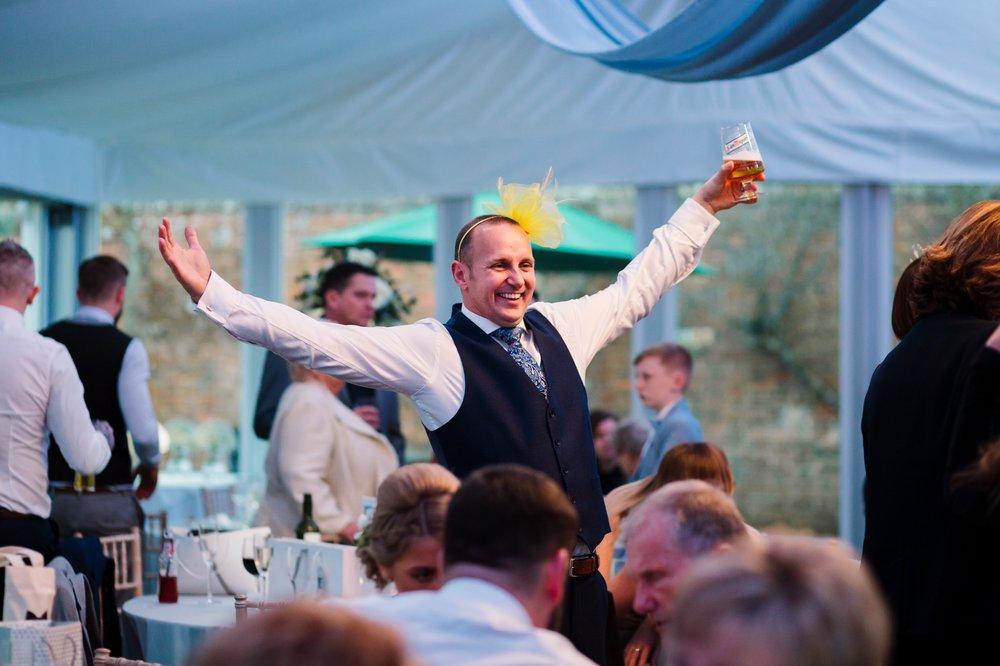 man wearing fascinator at fun wedding
