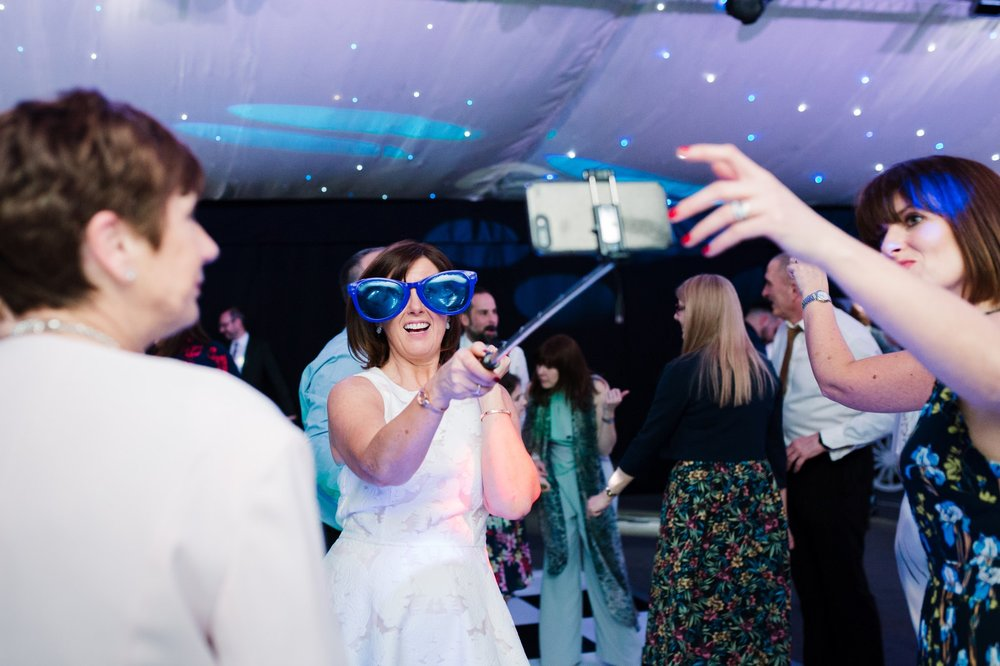 woman having selfie with huge glasses on at wedding