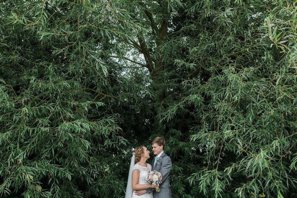 bride and groom under tree in rain