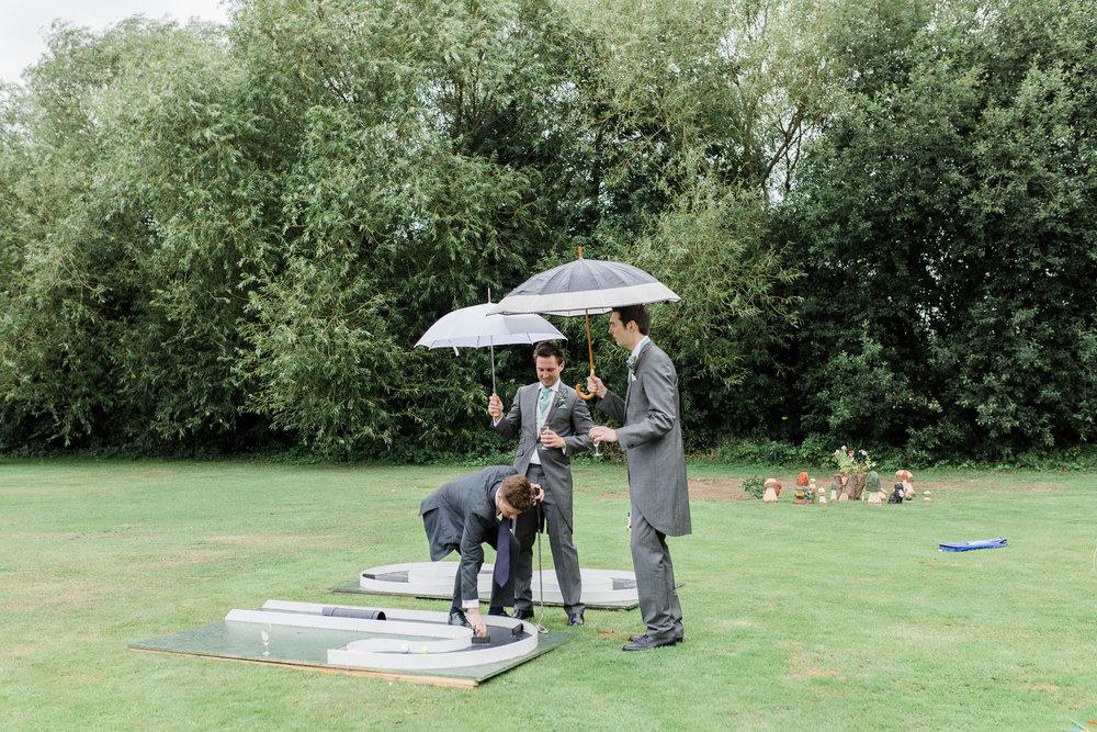 groomsmen playing garden games in the rain