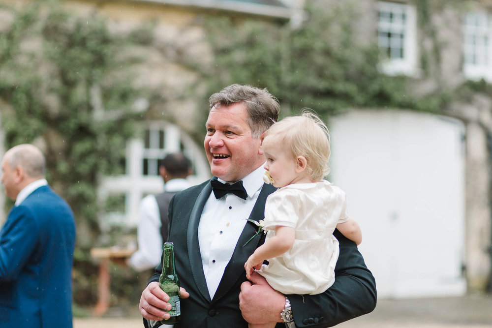 father of groom holding baby