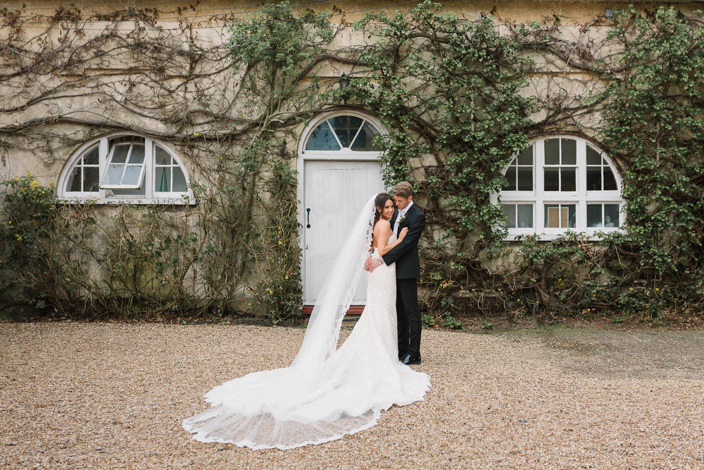 bride and groom in front of coach house at northbrook park wedding venue