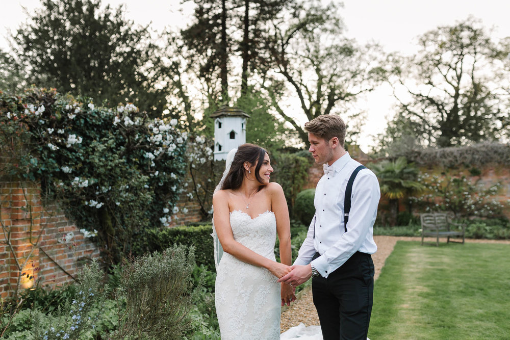 bride and groom walking together in gardens