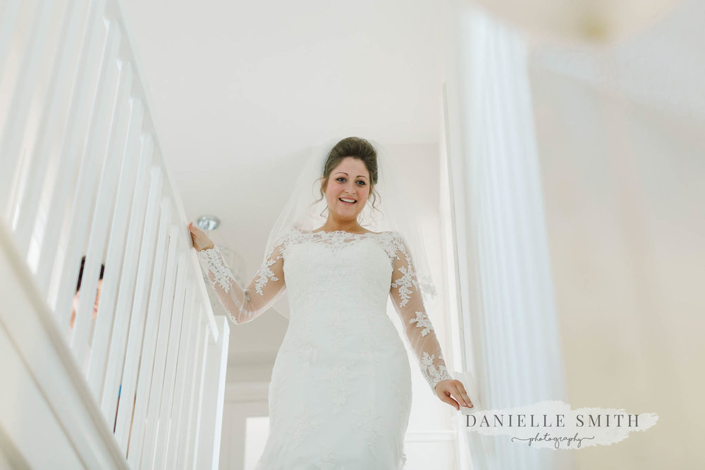 bride walking down stairs - elegant and romantic black tie wedding