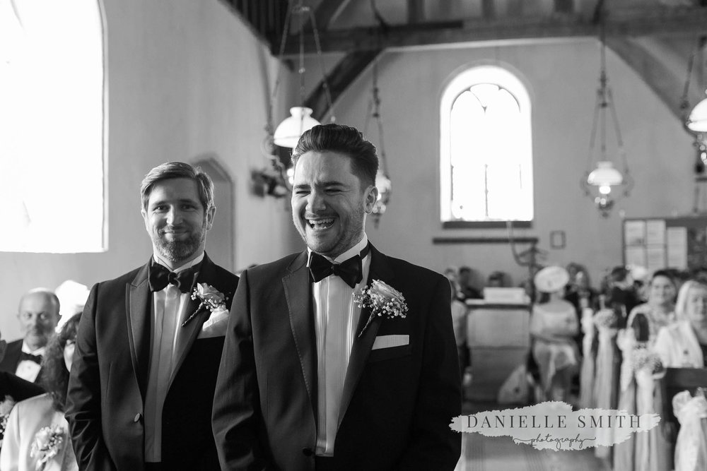 groom laughing while he waits for bride