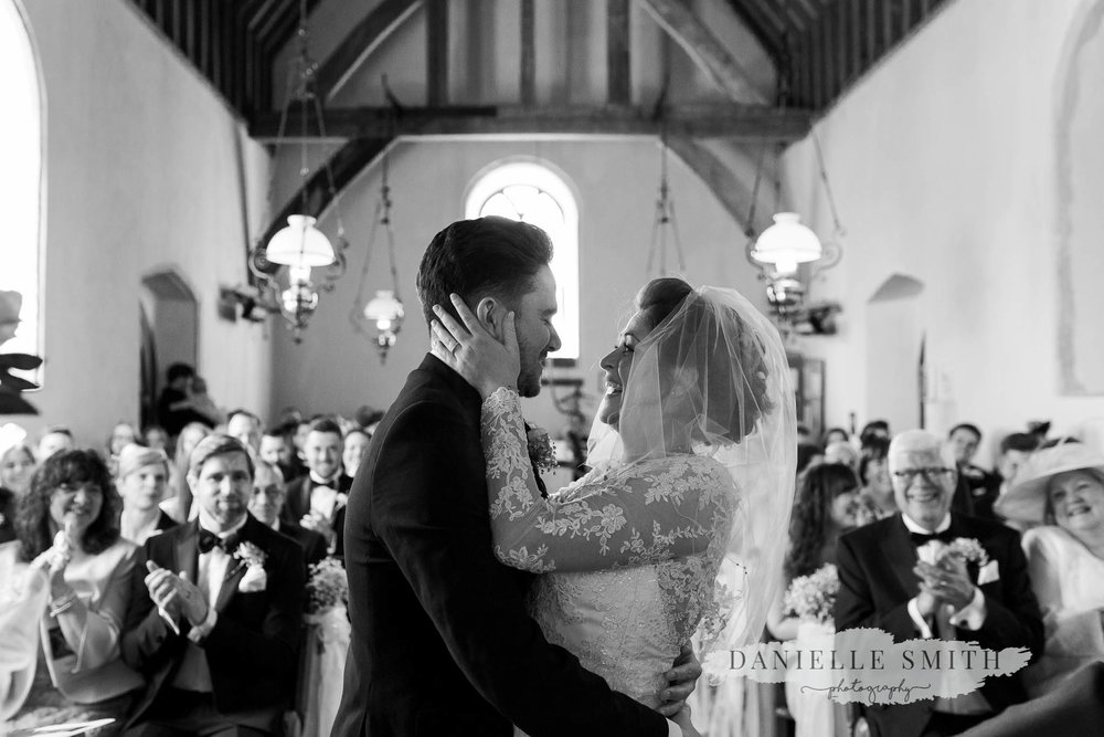 bride and groom first kiss in church