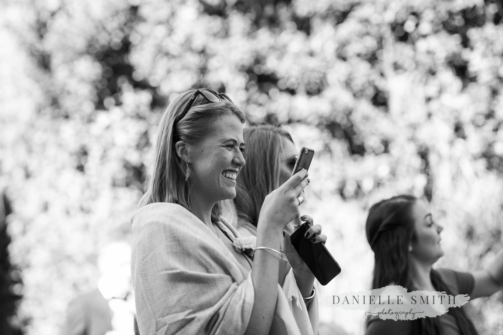 wedding guests taking photo on her phone