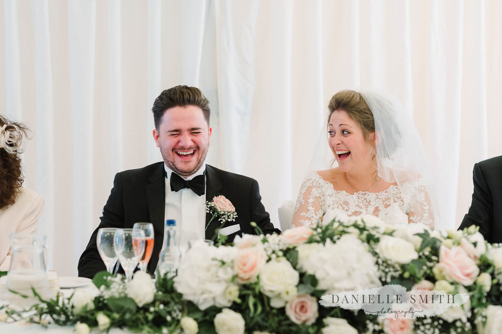 bride and groom laughing at best mans speech - mulberry house