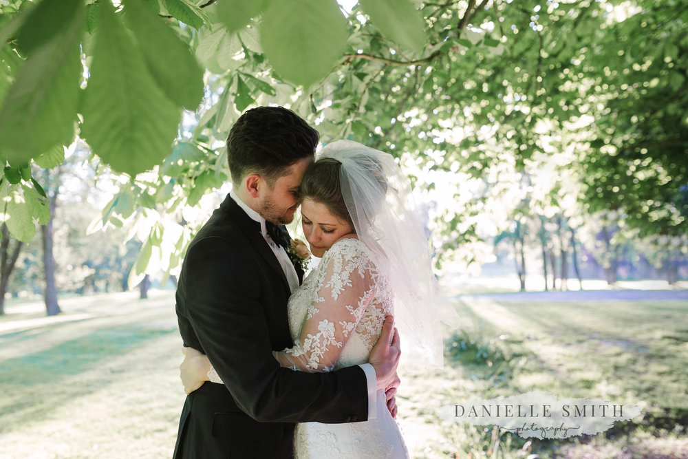 bride and groom snuggling under tree at mulberry house
