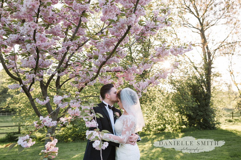 bride and groom with pink blossom at mulberry house
