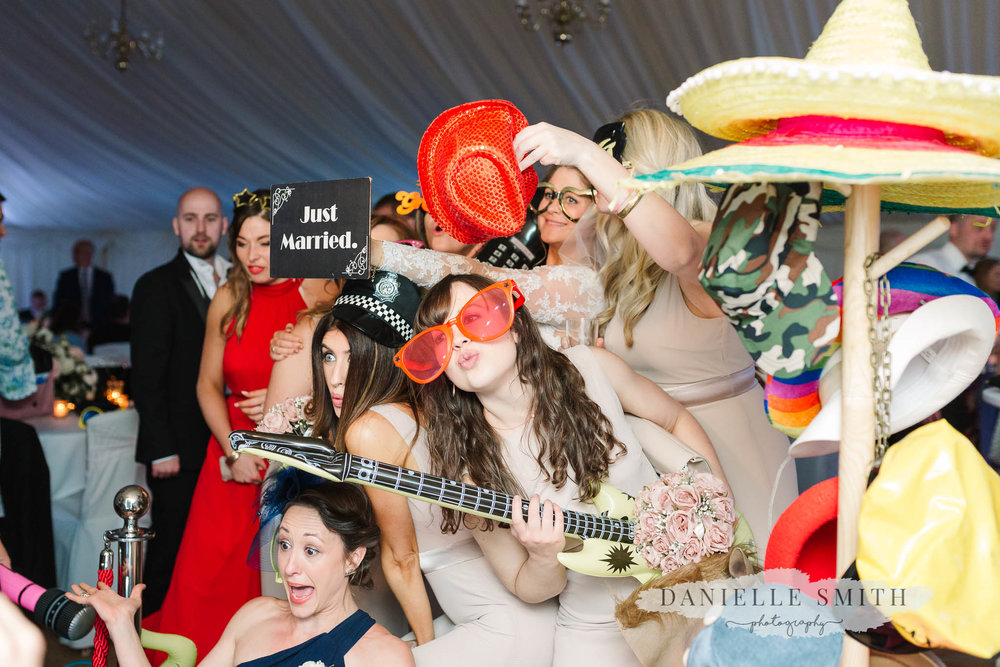 bride and bridesmaids in photo booth with props