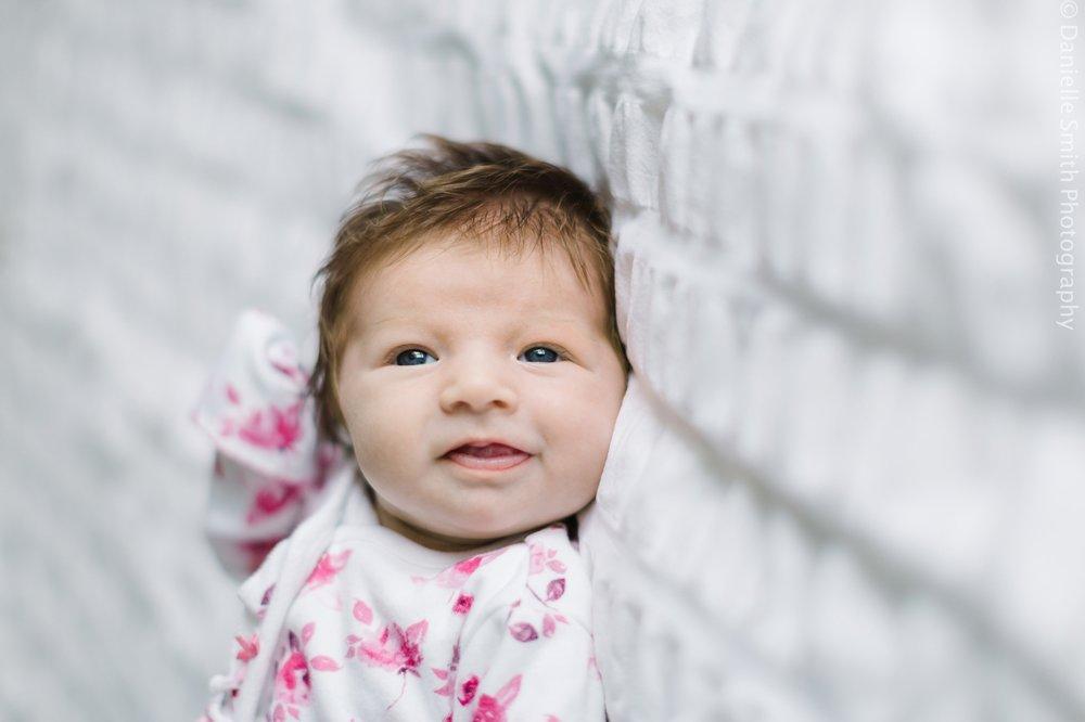 newborn baby in pink floral romper