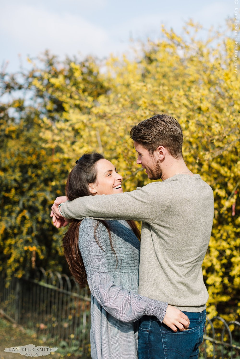 couple laughing and hugging in London park in spring