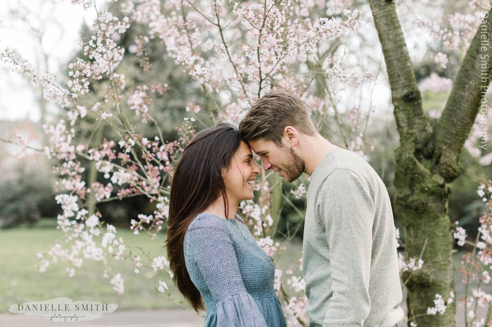 couple in front of blossom in Kensington gardens
