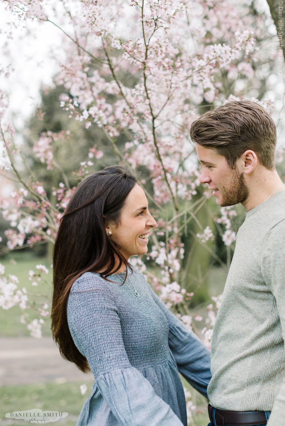 couple smiling with blossom tree - Kensington Gardens Pre-wedding Photography in Spring