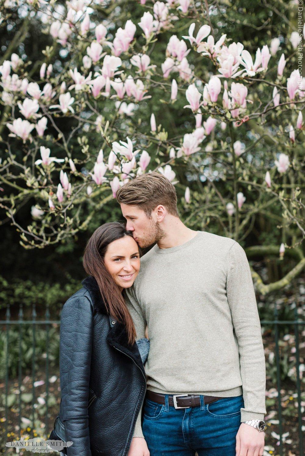 man kissing girlfriends head- Kensington Gardens Pre-wedding Photography in Spring