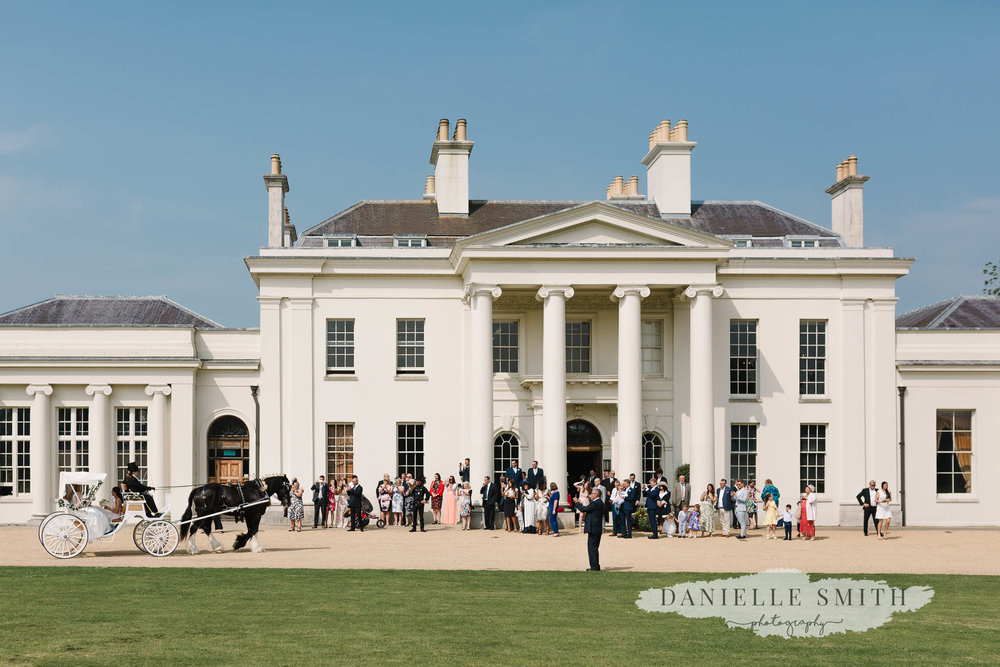 Country Estate Spring Wedding at Hylands House - horse and carriage arriving in front of venue and guests