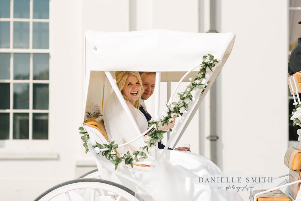 bride and groom leaving in  horse and carriage