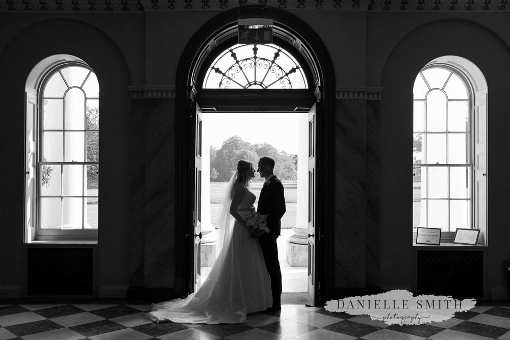 bride and groom inside doorway of hylands house