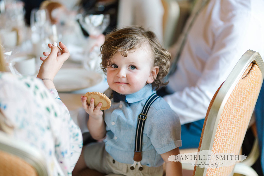 little boy eating biscuit at wedding
