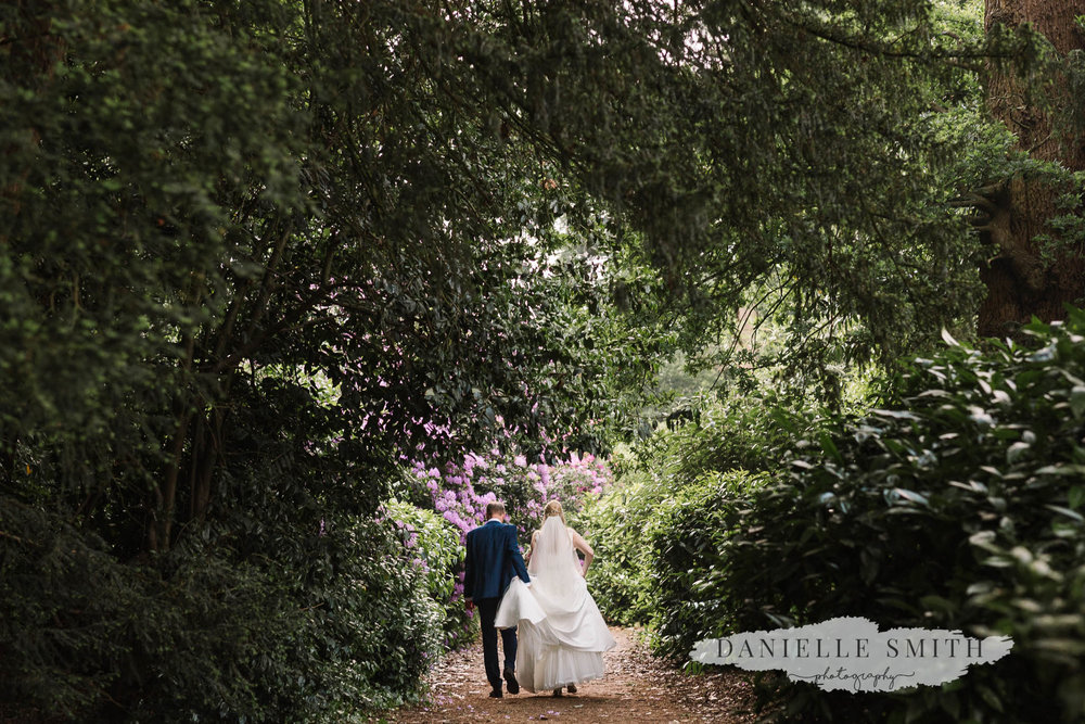 groom holding brides dress as they walk through gardens