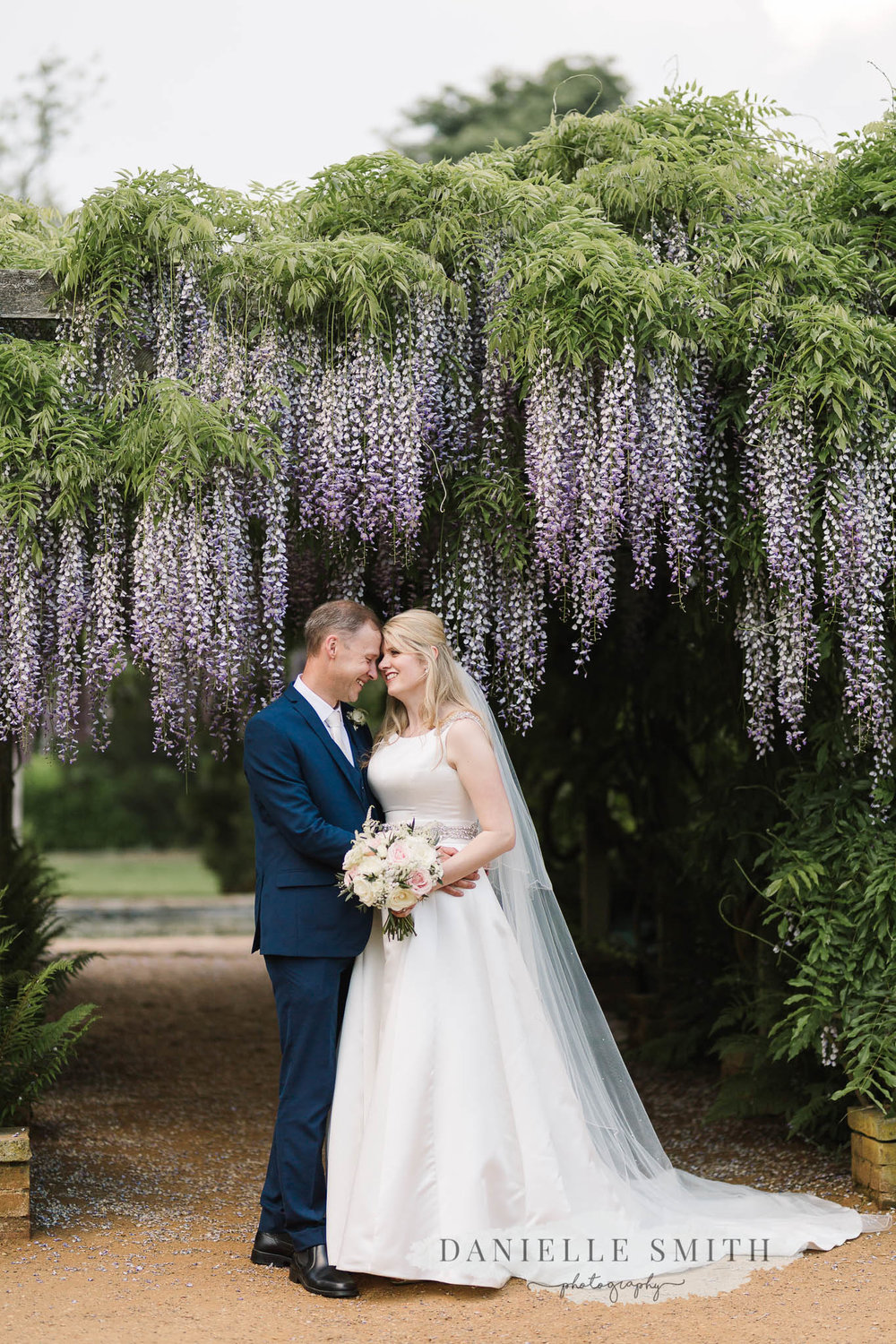 bride and groom with wisteria