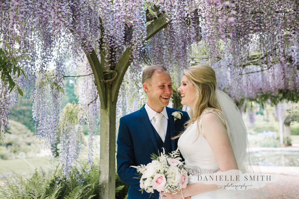bride and groom under wisteria at hylands house