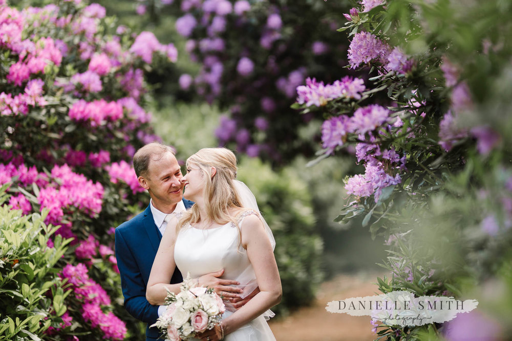 bride and groom with colourful flowers