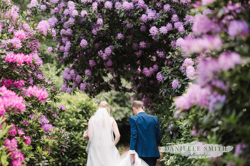 bride and groom walking through colourful gardens