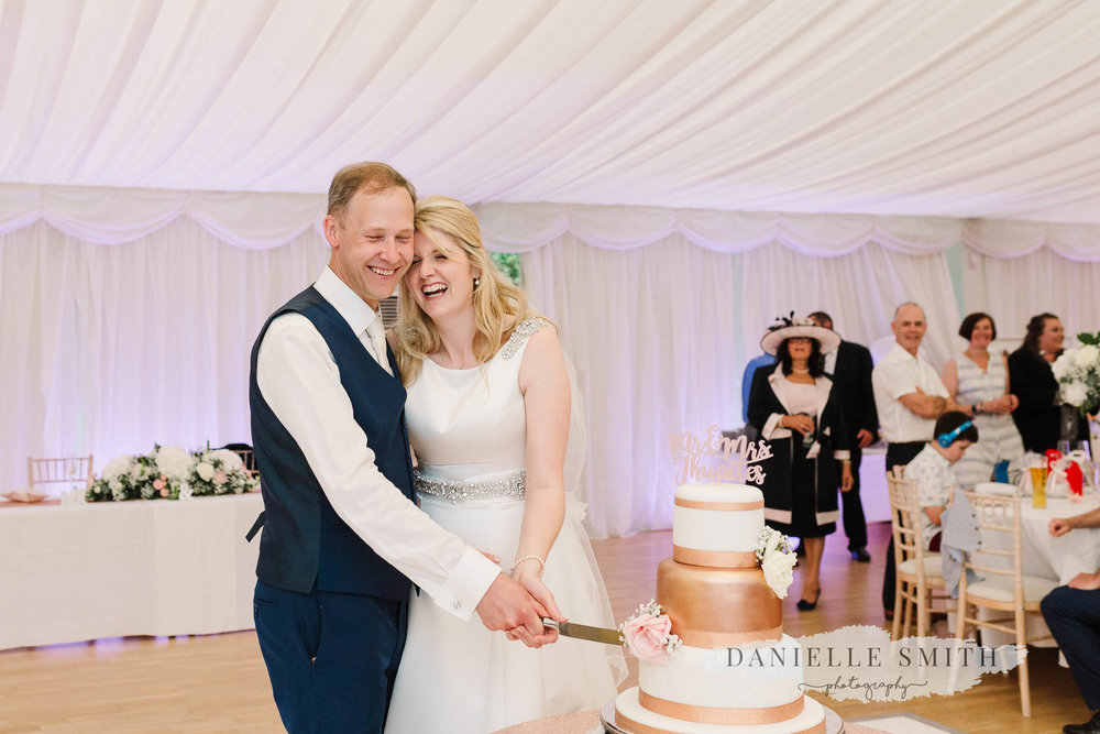 bride and groom laughing as they cut cake