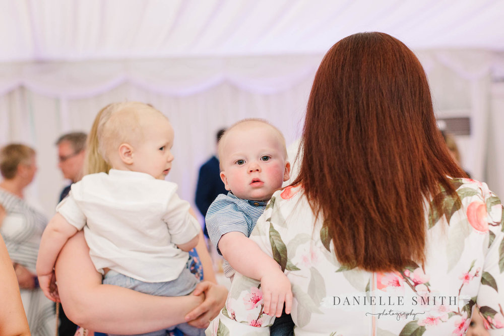 guests holding babies at wedding