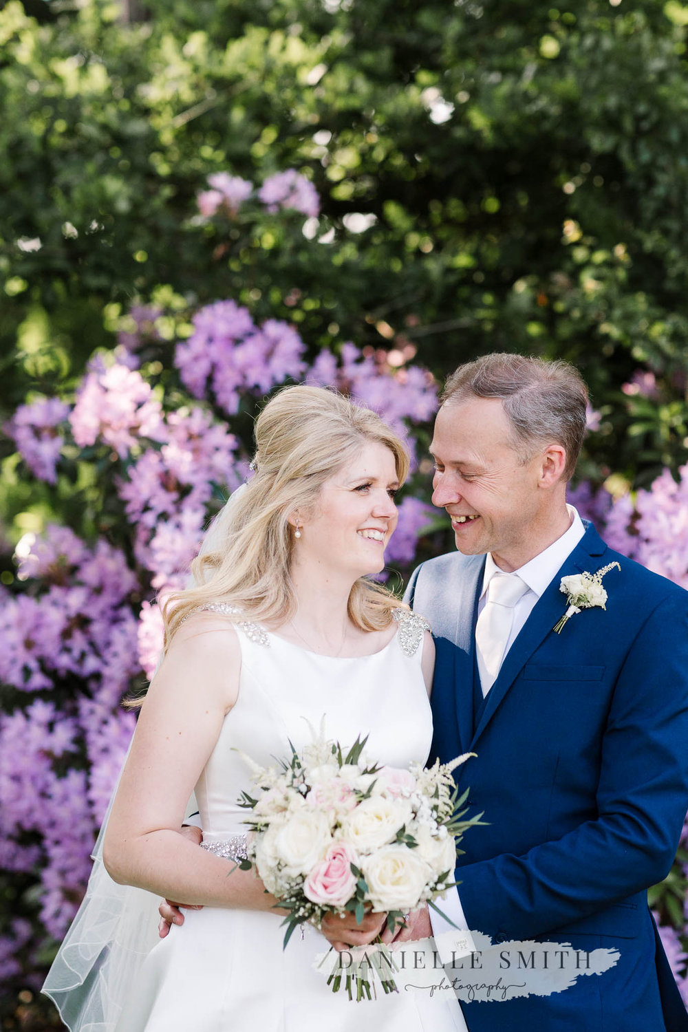 bride and groom laughing with purple flowers in background