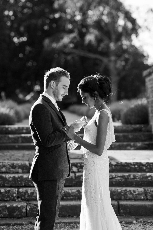 groom looking at brides necklace