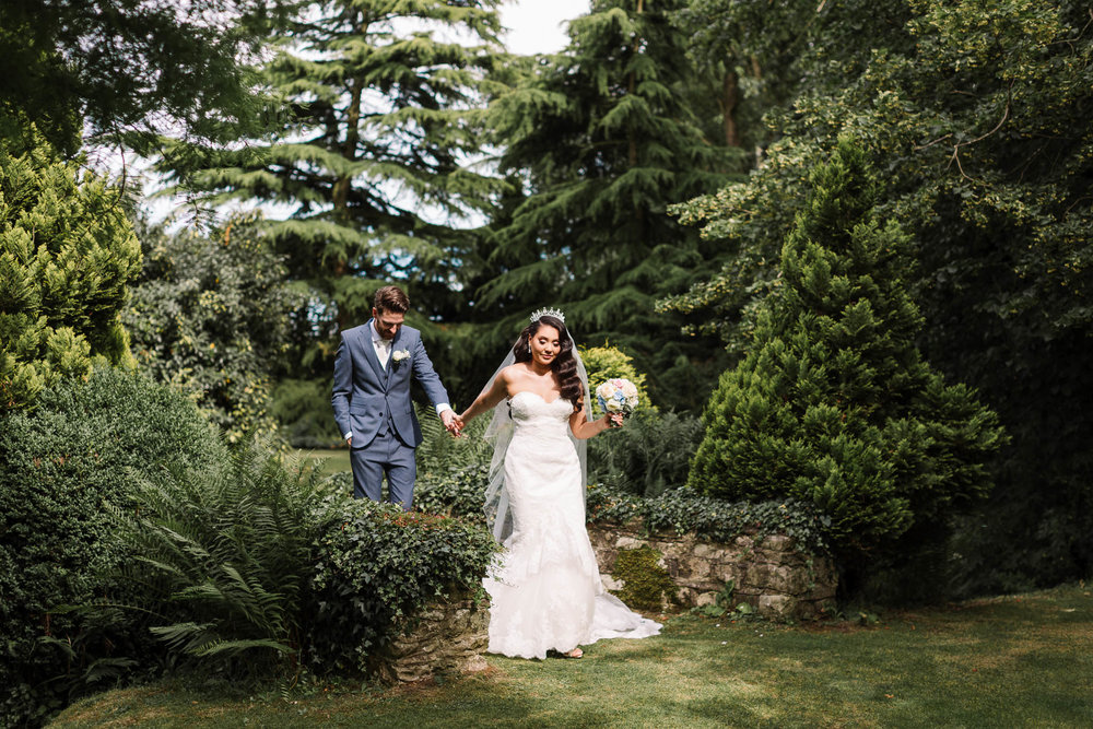 bride and groom walking through gardens at brewerstreet farmhouse wedding