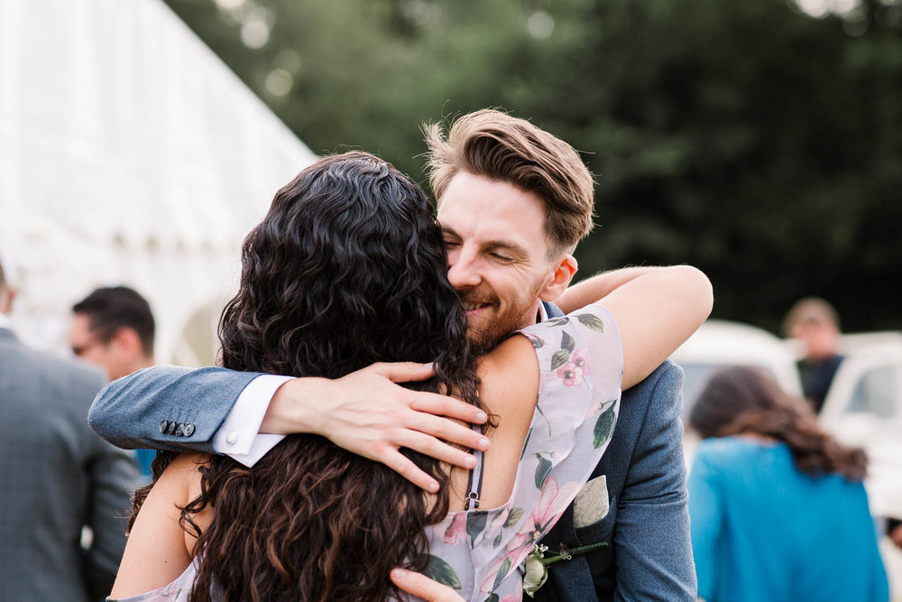 groom hugging guest at fun and relaxed wedding