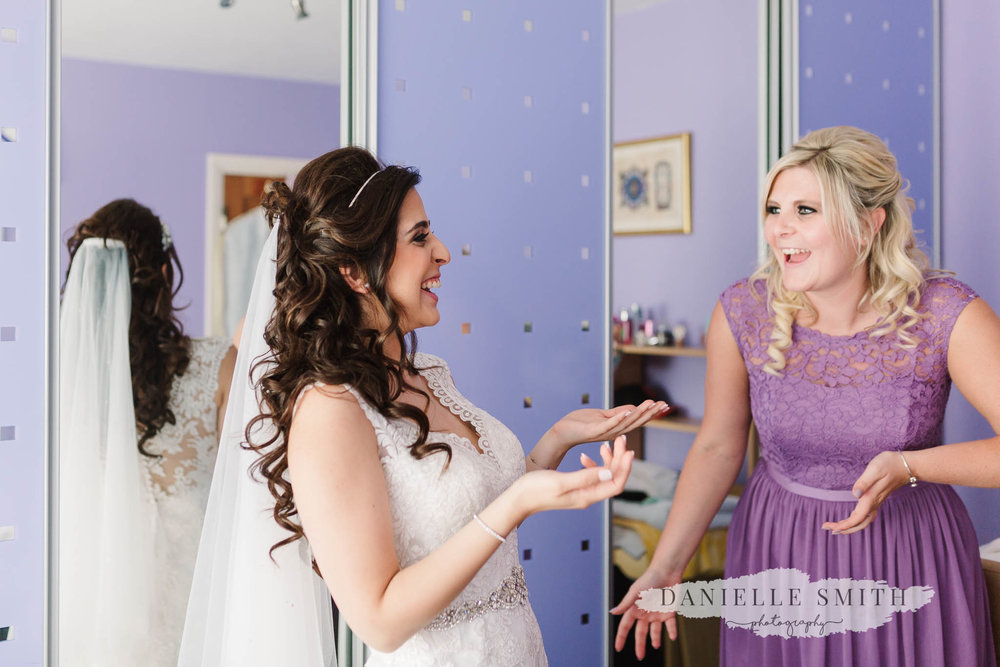 bride and bridesmaid laughing during prep