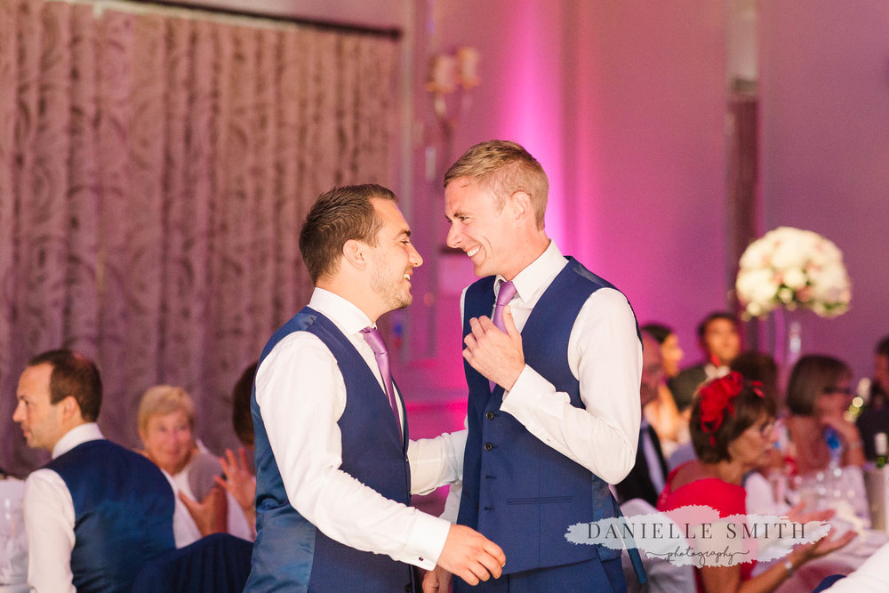 groomsmen laughing at wedding reception