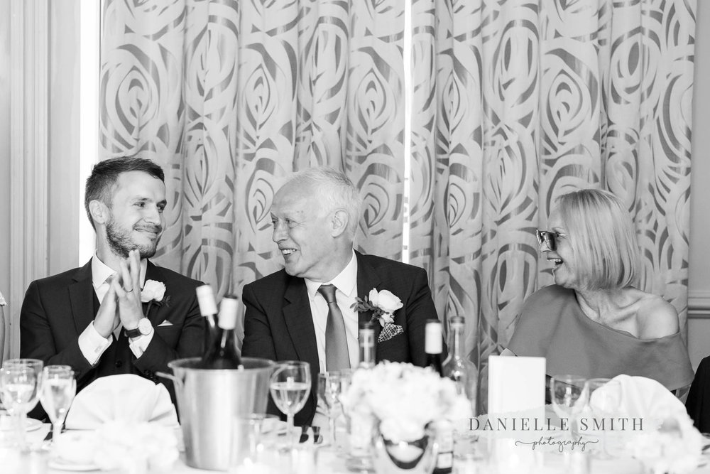 groom and his parents laughing at speeches