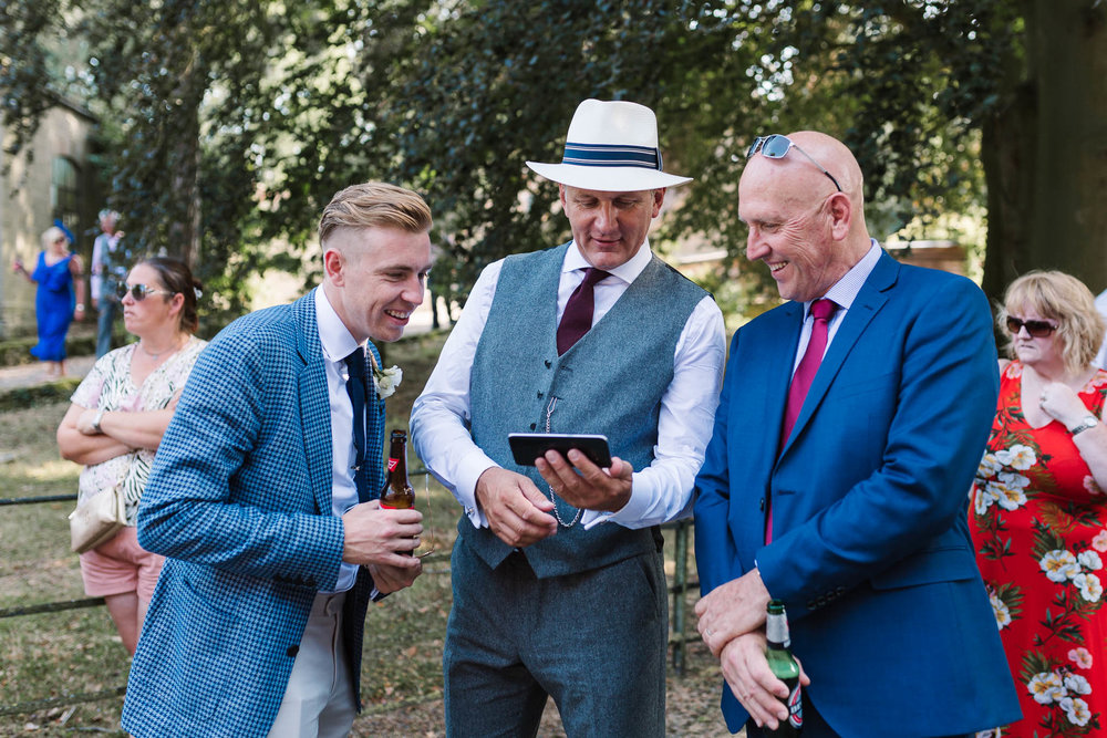 wedding guests laughing at phone