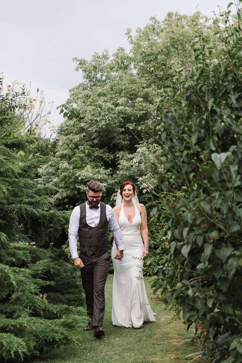 bride and groom walking through gardens - ENGLISH COUNTRY WEDDING AT SWARLING MANOR
