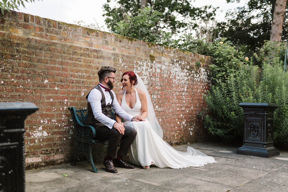 bride and groom sitting on bench at swarling manor