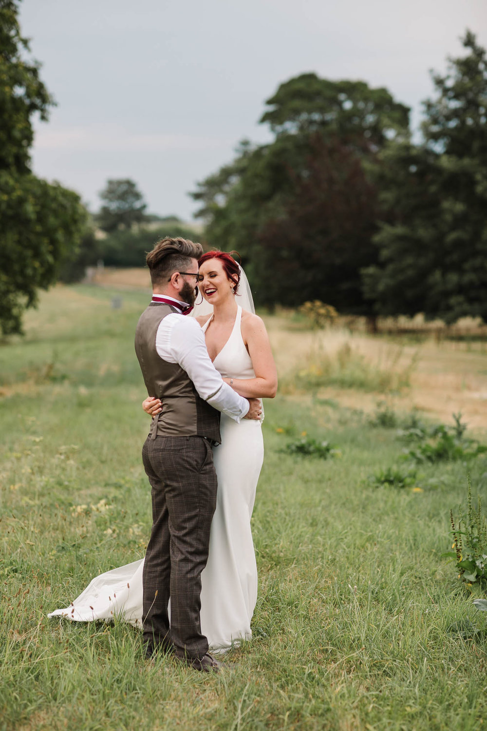 bride and groom laughing at english country wedding
