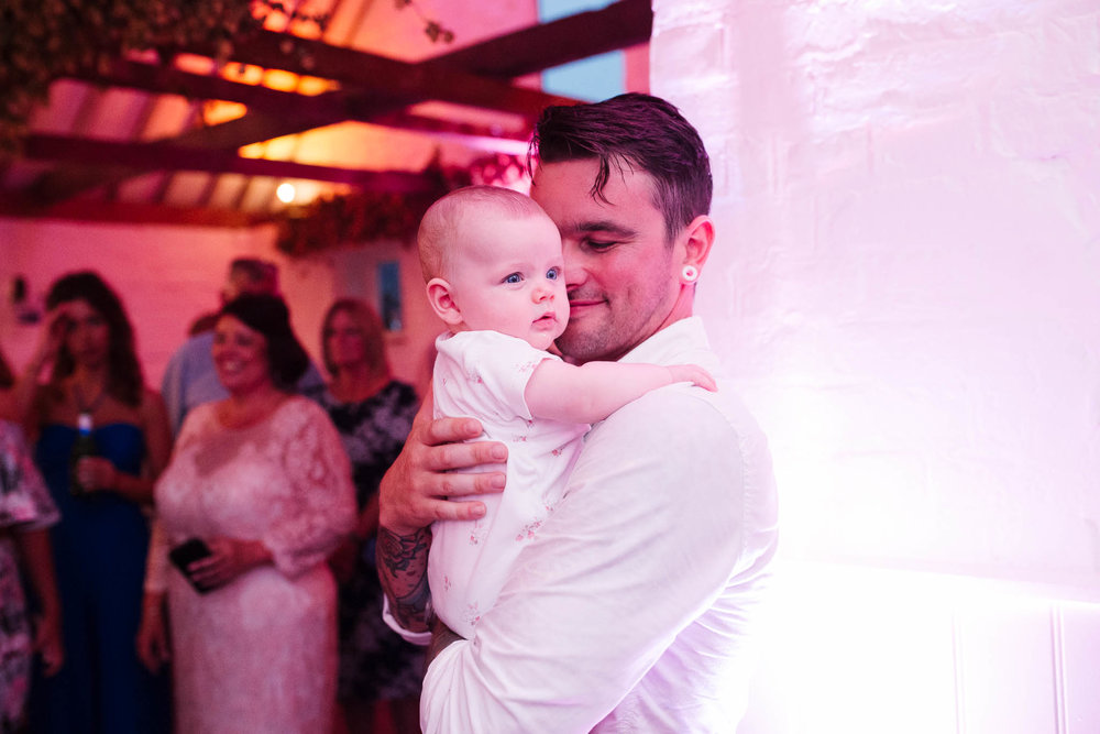 dad dancing with baby at wedding