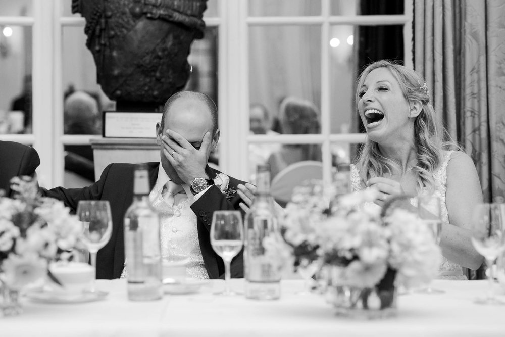 groom covering face and bride laughing during best man speech